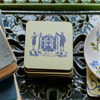 Blue and cream set of coasters featuring an illustration of Dick and Angel Strawbridge from Escape to the Chateau and 2021 banner