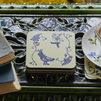 Blue and cream set of coasters featuring dancing pig chicken and bunch of grapes motif