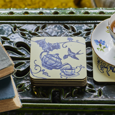 Blue and cream coasters with a motif featuring vintage teapot pouring tea alongside a bat and swallow