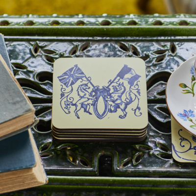 Set of four cream coasters featuring United Kingdom and France flag among a crest in blue